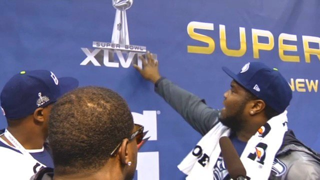 Members of the Seattle Seahawks explain to Sam Adams what they think the roman numerals for Super Bowl XLIX.