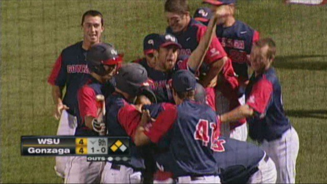 Caleb Wood is crushed by his teammates after scoring the winning run off a WSU wild pitch on Tuesday night.