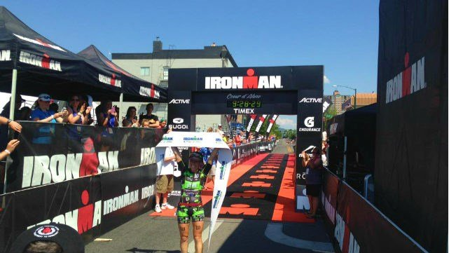 Heather Jackson raising the IRONMAN Coeur d'\Alene finish tape proudly after her first-ever IRONMAN win.