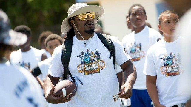 Marshawn Lynch coaching local at-risk youth at his football camp in the Bay Area, sans chicken wings. (Photo: Seahawks)